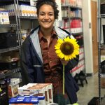 woman holding a sunflower at pantry behind donations