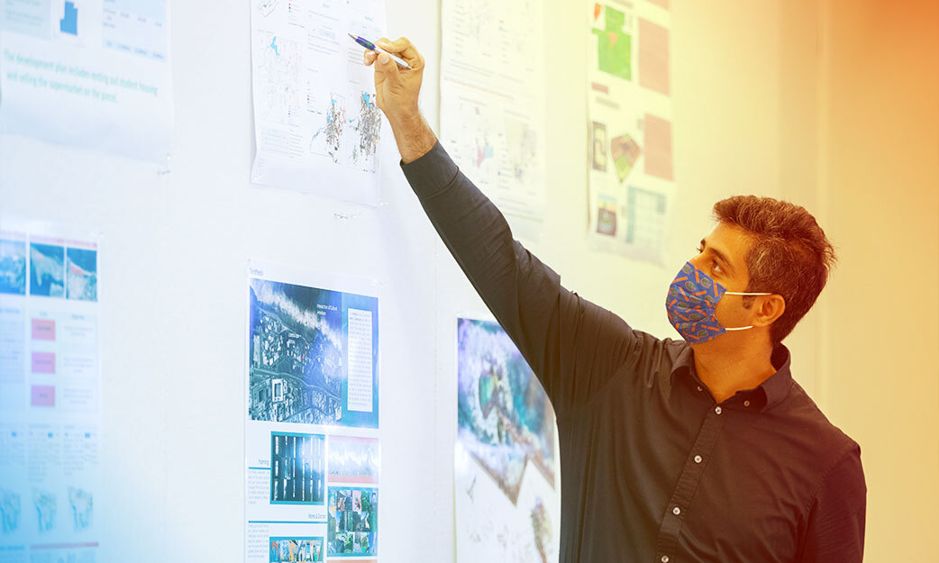 Man wearing mask while pointing to whiteboard
